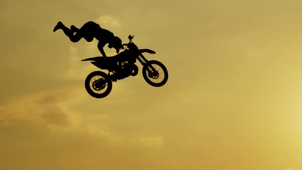 Pro motocross rider riding fmx motorbike, jumping big air kicker performing extreme stunt. Professional biker jumps no hander superman trick over golden sunset sky above trees Royalty-free stock video