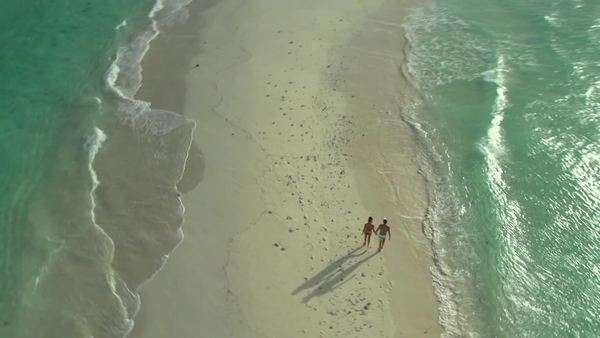 Aerial view of tourists walking on sand surrounded by water Rights-managed stock video