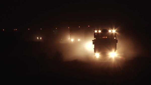 Wide shot of trucks traveling at night Rights-managed stock video