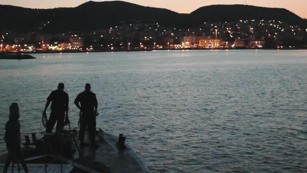 Wide shot of people on a fishing boat nearby a coastal town in Greece Rights-managed stock video