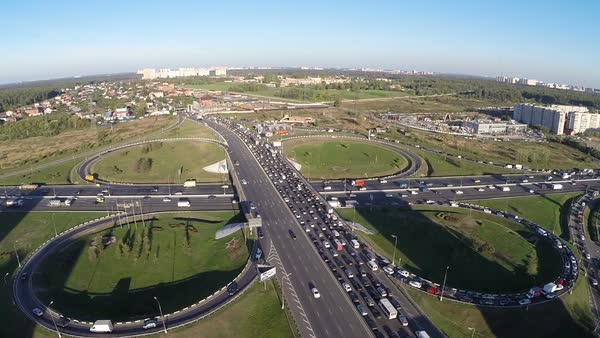 Aerial view of city traffic on highway typical cloverleaf interchange Urban transportation with traffic jams in industrial country side area Royalty-free stock video