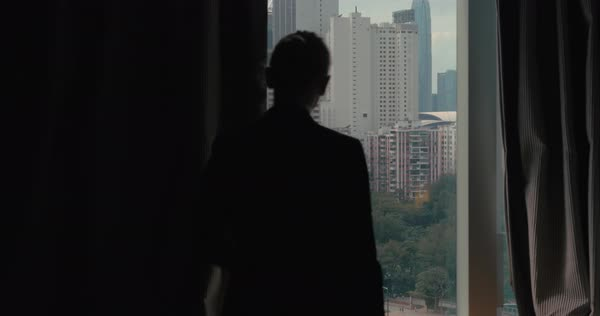 Clip of woman silhouette opening window curtains separately every side on the view of Hong Kong, China Royalty-free stock video