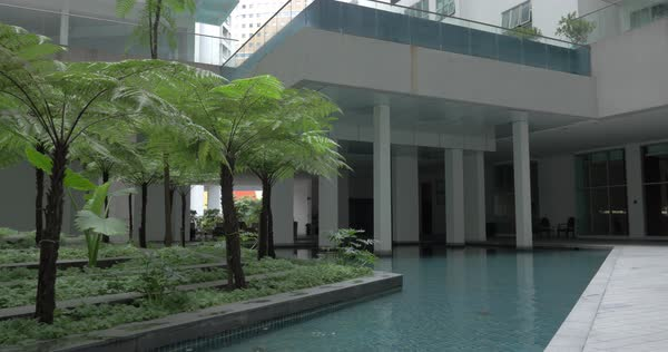 In Kuala Lumpur, Malaysia seen building and unusual fountain with trees, palms and orange lanterns Royalty-free stock video