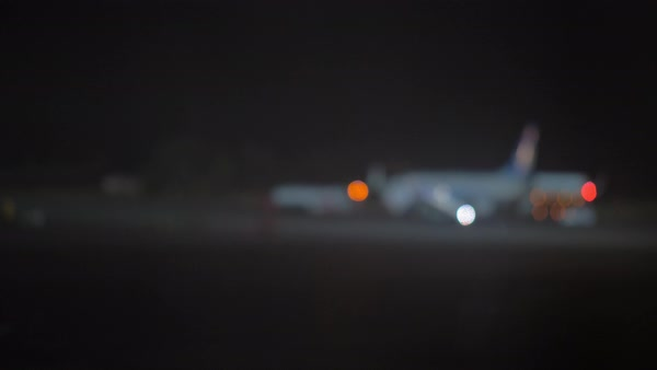 Slow Motion Defocused Shot Of Airplane And Pushback Tug In The Airport At Night Royalty