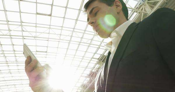 Low angle shot of a young businessman using smart phone in trade center or office builidng. Metal and glass roof with bright sun flare in background Royalty-free stock video