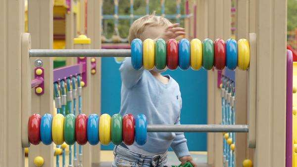 Little boy playing with an abacus with colourful rings on two bars in a childs playground as he learns to count Royalty-free stock video
