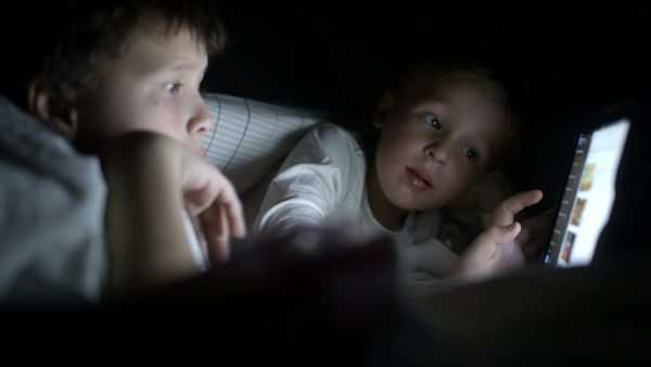 Two little boys in bed try to watch the film at night using the tablet Royalty-free stock video