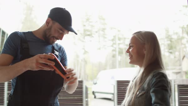 Beautiful homeowner opens the door to smiling delivery man and receives parcel after signing on electronic signature device Royalty-free stock video