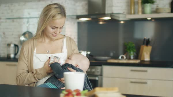 Beautiful young mother feed her cute child from a bottle Royalty-free stock video