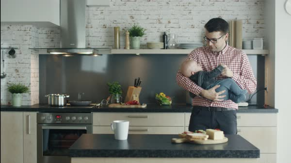 Young father strolls kitchen while holding and nursing his cute child Royalty-free stock video
