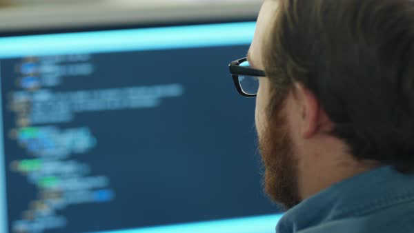 Close-up of a man's head in the background computer screen with code line is seen. Royalty-free stock video