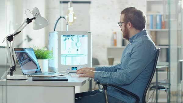 Young bearded developer uses 3d printer for modeling. he is sitting at his desk in a technologically modern office. Royalty-free stock video