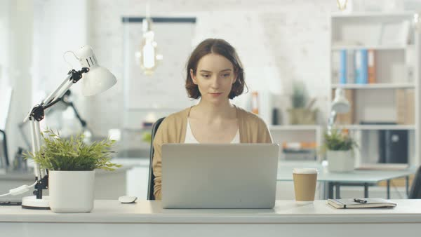 Portrait shot of a creative woman sitting at her desk. using notebook. she sits in a light and modern office. Royalty-free stock video