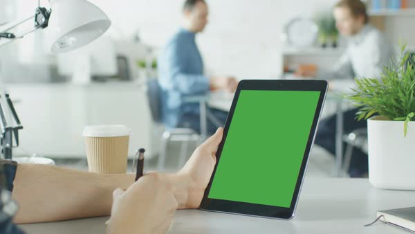 Close-up of a man's hands holding green screen tablet computer vertically and making notes with pen on sticky paper. In the background bright modern office with people working in it. Royalty-free stock video