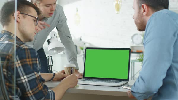 Three creative men discuss business around green screened laptop. They're in bright modern office. Royalty-free stock video