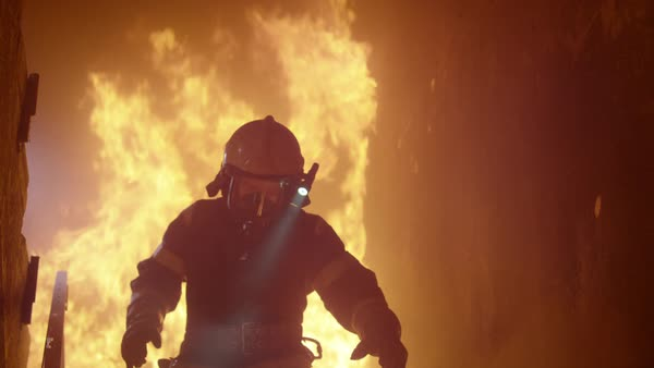 Firefighter with flashlight on his helmet runs down the burning stairs Royalty-free stock video