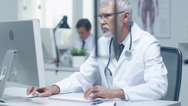 Close-up of a senior doctor and his assistant working at desktop computers. Sitting in brightly lit office. Royalty-free stock video