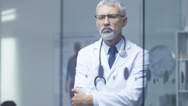 Portrait of a white haired senior doctor thinking about patient's diagnosis. Royalty-free stock video