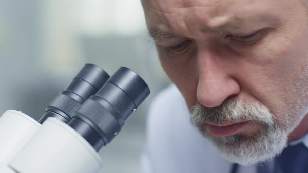 Close-up of a senior male doctor conducting health issue research through microscope. Royalty-free stock video