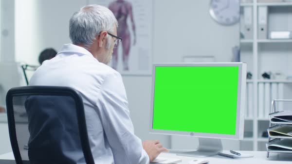 Senior medical doctor working on a mockup green screen personal computer. His assistant works in the background. Office has a touch of modern minimalism. Royalty-free stock video