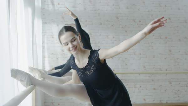 Three young and beautiful ballerinas stretching legs at ballet barre Royalty-free stock video