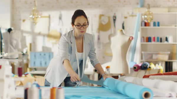 Beautiful female fashion designer straightens roll of blue fabrics and lays out templates on it. She works in a light colorful studio full of various clothes, fabrics and sketches on the wall. Royalty-free stock video