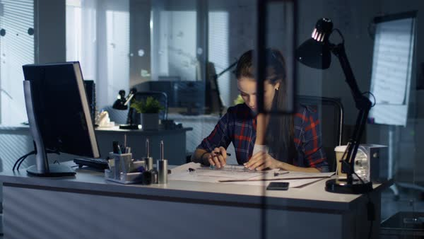 Beautiful female design engineer working on drafts late at night Royalty-free stock video