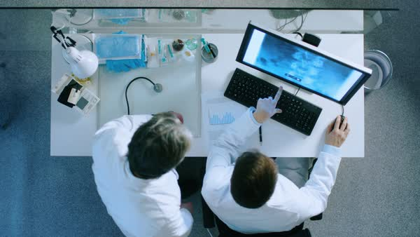Top view of two doctors at the working desk discussing patient's x-ray shown on a monitor screen. They come to conclusion and doctors writes down diagnose on a paper. Royalty-free stock video