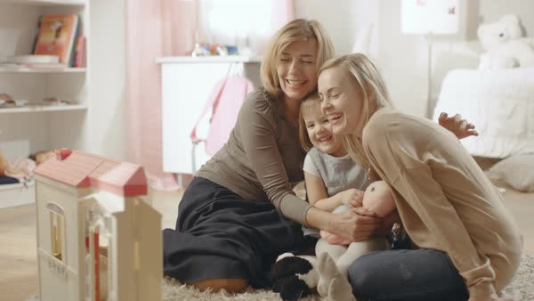 Grandmother, mother and her little cute daughter have a big hug. They're in a children's room which is pink and full of toys. Royalty-free stock video