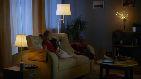 In the evening cute little girl is sitting in living room on a sofa, she watches television. She holds her soft toy, room lights are on. Royalty-free stock video