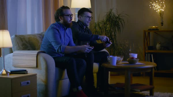 In the evening two friends are sitting on a sofa in the living room and playing competitive video games. Royalty-free stock video