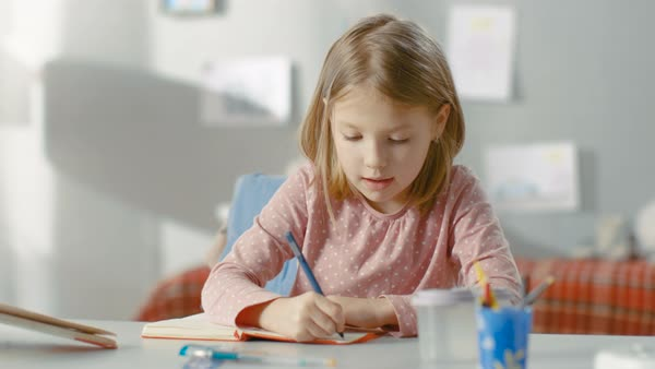 Smart little girl writes in her diary while sitting in her room. Royalty-free stock video