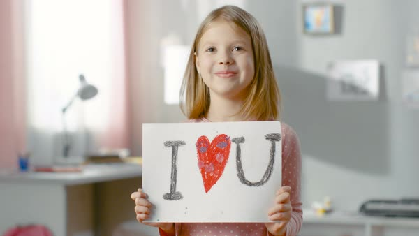 "Cute young girl shows fun drawing ""I love you"" with heart in the middle. Royalty-free stock video"
