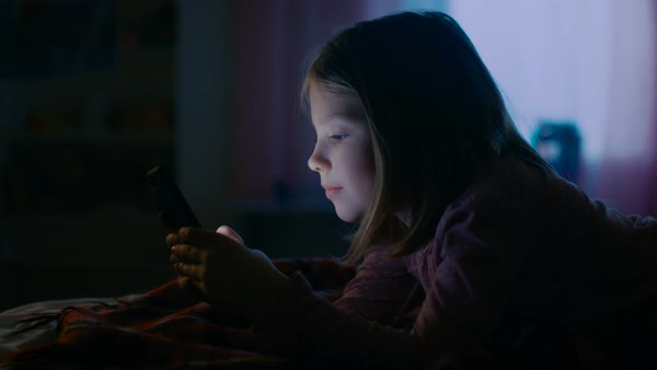 Cute little girl in her room at night, lies on a bed uses smartphone. Her night lamp turned on. Royalty-free stock video