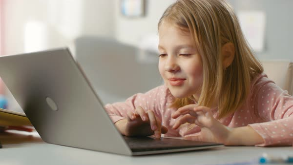 Cute young girl uses laptop computer with interest while sitting at the table in her light room. Royalty-free stock video