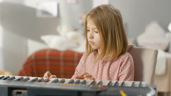 Talented young girl learns how to play synthesiser. She's in her cozy room. Royalty-free stock video