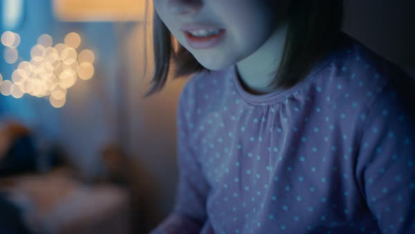 Smart young girl in her bedroom late at night sits on her bed with laptop and types something interesting. Her night lamp is on. Royalty-free stock video
