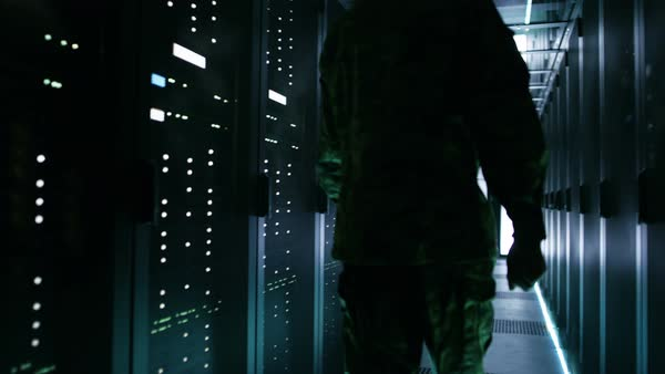 Soldier walks into data center through sliding doors and walks along rows of working rack servers. Royalty-free stock video