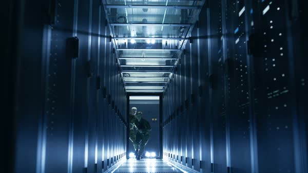 Security alarm with flasher triggered in data center. Two military men enter sliding doors and run through corridor full of server racks. Royalty-free stock video
