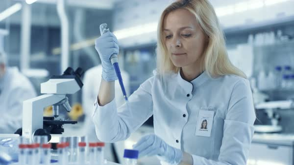 Female research scientist uses micropipette filling test tubes Royalty-free stock video