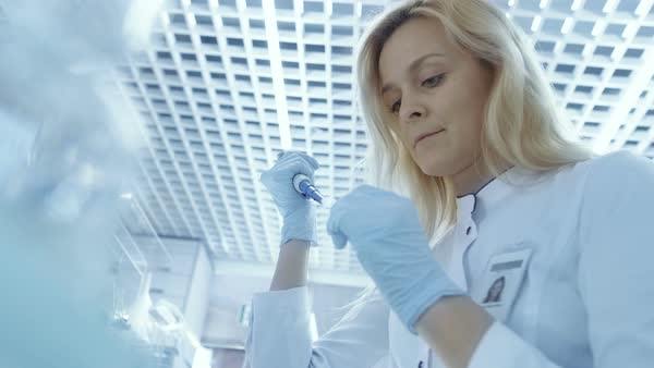 Low angle shot of medical research scientist uses micropipette to fill test tubes Royalty-free stock video