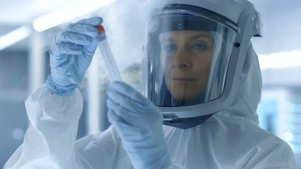 Medical virology research scientist in a hazmat suit with mask, she inspects test tube with isolated virus string from refrigerator box Royalty-free stock video
