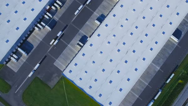 Aerial top view of industrial warehouse/ storage building/ loading area with solar panels on the roof and many trucks loading/ unloading merchandise Royalty-free stock video