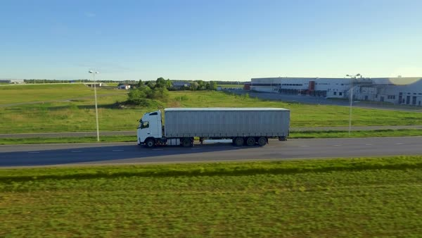 Aerial side view of white semi truck with cargo trailer moving on the highway Royalty-free stock video