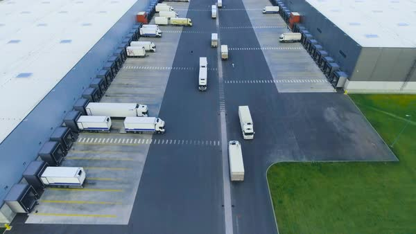 Aerial shot of industrial warehouse/ storage building/ loading area where many trucks are loading/ unloading merchandise Royalty-free stock video