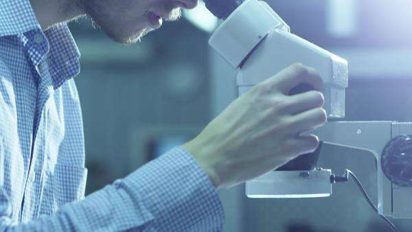 Engineer inspects detail quality under microscope on factory. Royalty-free stock video
