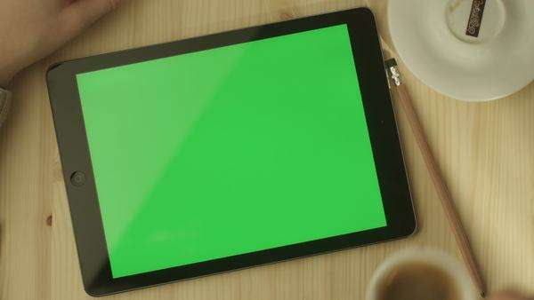 Tablet with green screen laying on a table landscape mode. Royalty-free stock video