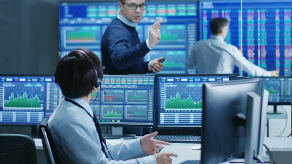 In the Network Operations Senior Trader Dictates Stock Numbers to Their Operator who Makes Call with a Headset. In the Background Traders Discuss Data Shown on Monitors.  Royalty-free stock video