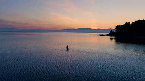 Aerial Shot of a Beautiful Woman with on a Standup Paddleboard. Woman Silhouette with Pink Sunset and Coastal Hills Visible. Royalty-free stock video