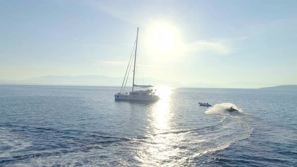 Aerial View of the White Sailing Catamaran Yacht and Jet Ski Driving Near by. Beautiful Weather with Calm Mirror Like Sea and Sun Shining. Royalty-free stock video